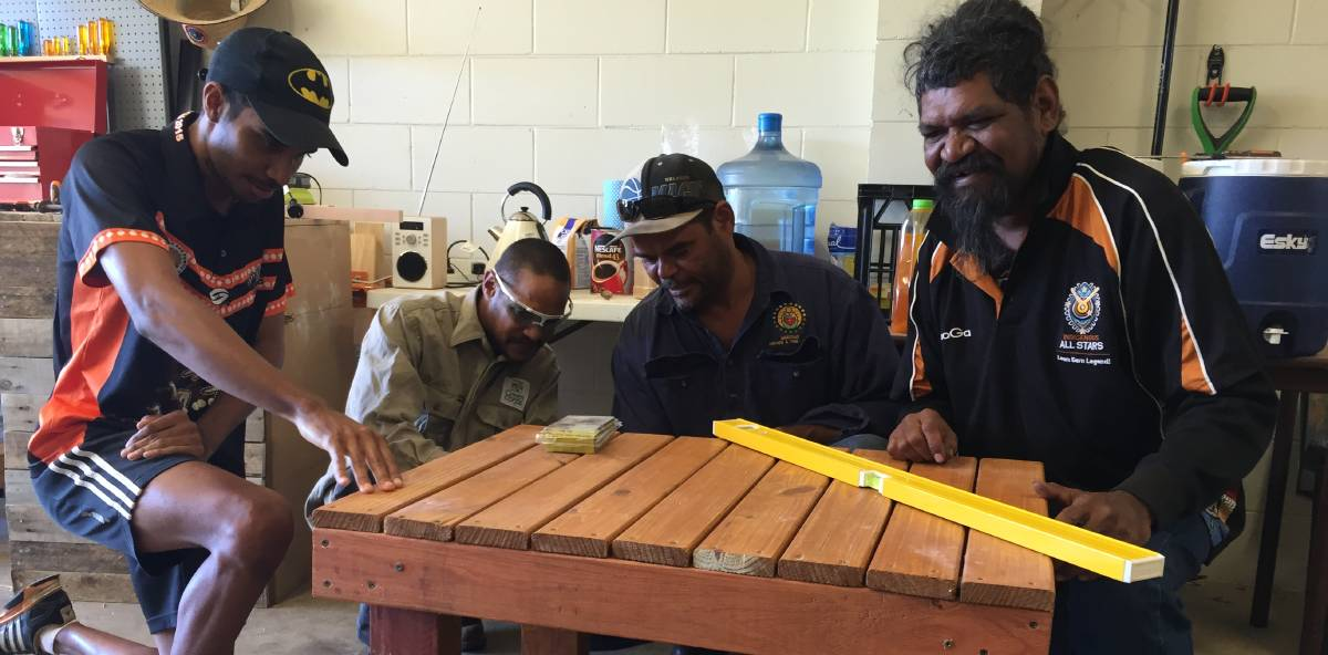 Looking busy: Men's Shed members Kale Johnson, Juhani Mursunen, Gary Hartman and Troy Wilde make a table from a crate. Photo: Chris Burns.